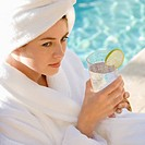 Woman wearing robe and towel on head drinking from glass next to pool