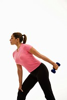 Side view of mid adult woman wearing pink shirt exercising with dumbbell.