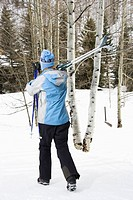 Rear view of mid adult Caucasian female skier wearing blue ski clothing walking and carrying skis on shoulder.