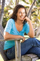 Female sitting in chair with hand on chin smiling