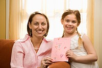 Caucasian girl giving mid adult mother a drawing and looking at viewer.