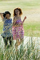 Two young women walking arm in arm outdoors, both laughing