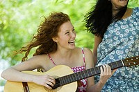 Young woman playing acoustic guitar outdoors, laughing