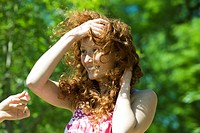 Young woman with red hair outdoors on windy day