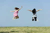 Two young women jumping in midair outdoors, rear view