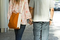 Young couple walking hand in hand on sidewalk, rear view, cropped