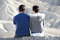 Couple sitting on stone wall in desert rear view