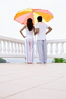 Young couple standing under parasol and looking at view (thumbnail)