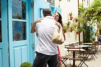 Couple hugging outside café (thumbnail)