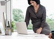 Businesswoman sitting on table and using laptop (thumbnail)