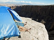 Couple sleeping in tent by cliff, high angle view, Moab, Utah, USA