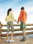 Young couple holding hands and looking at view by fence