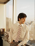 Young businessman looking through office window