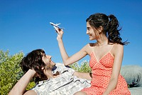 Young man looking at girlfriend playing with toy airplane