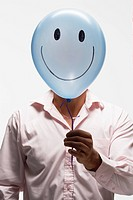 Man holding balloon with smiley face in front of his face