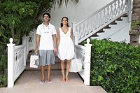 Young couple with luggage standing at resort