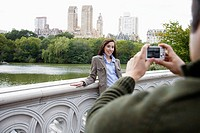 Man photographing woman on footbridge