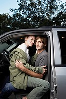Woman sitting on man's lap in car portrait