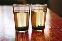 Two glasses of tea with tea leaves steeping