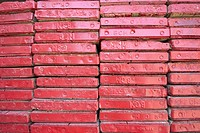 Close up ends of stacked red painted scaffold boards
