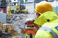 Surveyor using a theodolite on a construction site