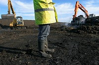 Legs of site warden with tracked excavator on landfill (thumbnail)