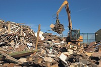 Excavator with grab extension segragates construction waste on a Recycling plant