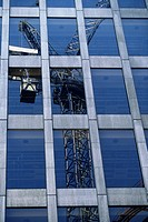 Tower crane reflected in glass facade of modern high rise building