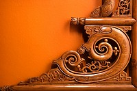 Ornate wooden Asian furniture carving against orange wall