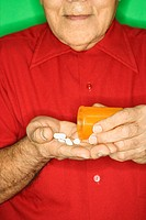 Mature adult Caucasian male emptying pill bottle into hand