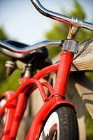 Image of red bike leaning against railing of boardwalk