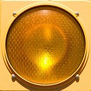 Closeup of yellow traffic stoplight (thumbnail)