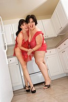 Caucasian young women in sexy red lingerie smiling and dancing in kitchen