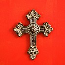 Ornate religious cross hanging on red wall