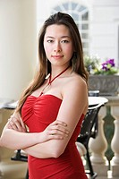 Taiwanese mid adult woman in red dress with arms crossed looking at viewer