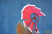 Old red broken windmill against rusted blue corrugated metal building