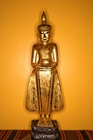 Golden wooden Buddha statue from Myanmar against yellow wall