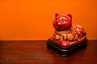 Chinese red cat statue against orange wall
