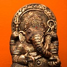 Statue of Hindu elephant Ganesha against orange wall