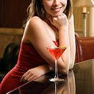 Taiwanese mid adult woman in red dress smiling and standing at bar with drink