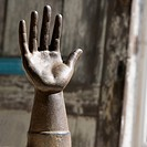 Metal statue of hand against wooden background
