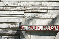 Sign on old white peeling building reading ´No smoking please!´.
