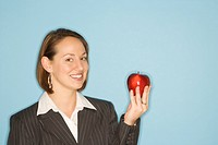 Caucasian businesswoman smiling holding red apple