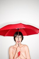 Shirtless young Caucasian woman holding red umbrella and looking up