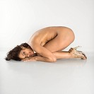 Portrait of attractive nude woman curled over on floor against white background