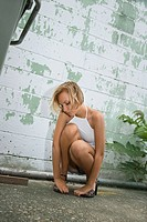 Caucasian mid_adult blonde woman kneeling beside building in alley