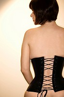 Rear view portrait of young Caucasian woman wearing corset