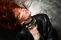Partially nude Caucasian woman in leather jacket with long hair blowing