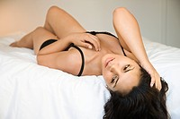Hispanic young adult woman in lingerie lying on bed with hand in hair