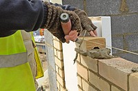 Close up of bricklayer's hands applying mortar on a Brickwall